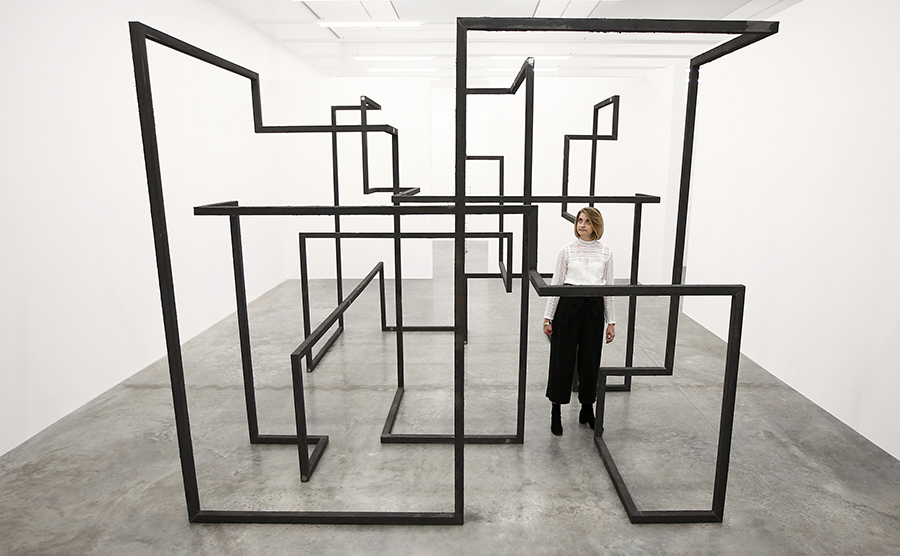 "A member of the gallery staff poses for a photograph with a piece called ""Run"", by artist Antony Gormley, which forms part of an exhibition entitled ""Fit"", at the White Cube gallery in London, Britain September 29, 2016.   REUTERS/Peter Nicholls"